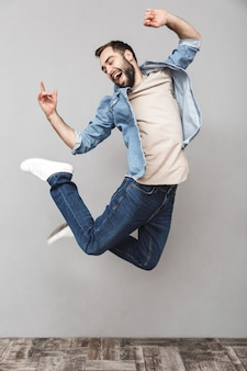 Full length portrait of a happy young man wearing shirt jumping over gray wall, celebrating