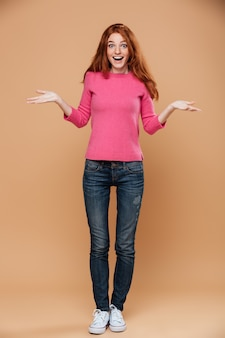 Full length portrait of a happy young redhead girl with open hands