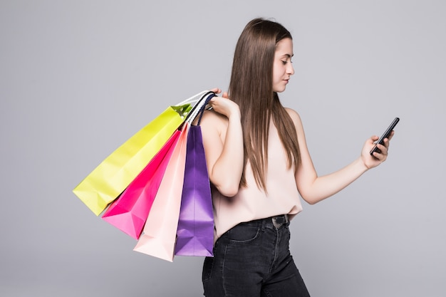 Full length portrait of a happy young woman holding shopping bags and mobile phone on a white wall
