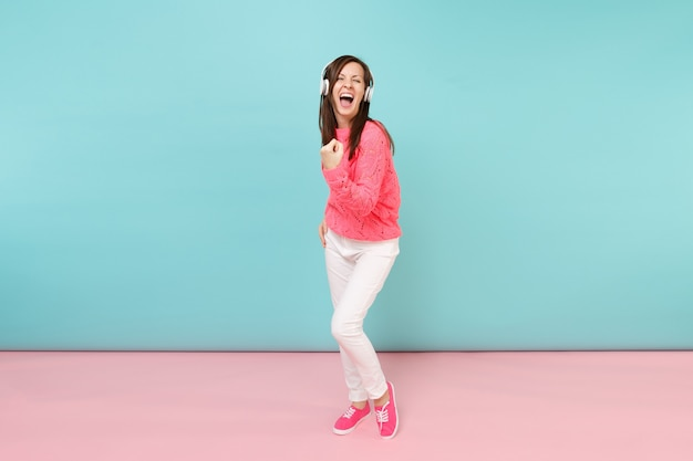 Full length portrait of happy young woman in knitted rose sweater, white pants, headphones