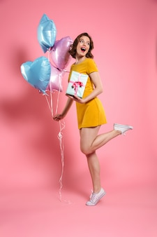 Full length portrait of happy young woman in yellow dress holding gift box and colorful balloons, looking aside