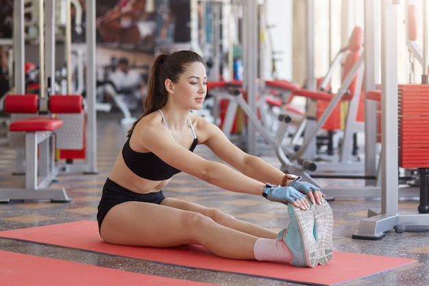Full length portrait of healthy motivated sportwoman stretching muscles while sitting on floor