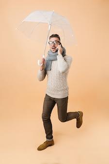 Портрет в полный рост, если красивый мужчина, одетый в свитер и шарф, идет под зонтиком, изолированным над бежевой стеной, разговаривает по мобильному телефону
