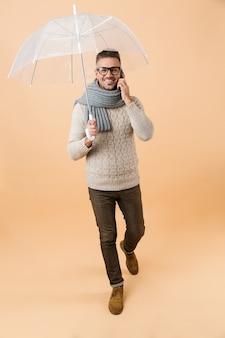Портрет в полный рост, если счастливый человек, одетый в свитер и шарф, идет под зонтиком, изолированным над бежевой стеной, разговаривает по мобильному телефону