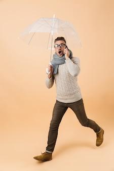 Портрет в полный рост, если шокированный мужчина, одетый в свитер и шарф, идет под зонтиком, изолированным над бежевой стеной, разговаривает по мобильному телефону