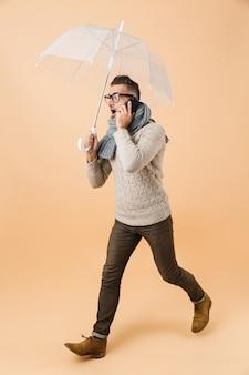 Портрет в полный рост, если удивленный мужчина, одетый в свитер и шарф, идет под зонтиком, изолированным над бежевой стеной, разговаривает по мобильному телефону