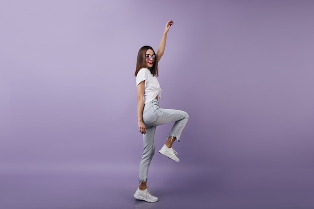 Full-length portrait of inspired female model in denim pants standing on one leg. brunette woman dancing with pleasure.