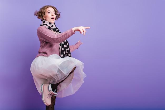 Ritratto a figura intera della ragazza ispirata in gonna lussureggiante in posa su una gamba sola sul muro viola. graziosa giovane donna caucasica in cappello e sciarpa lunga divertendosi