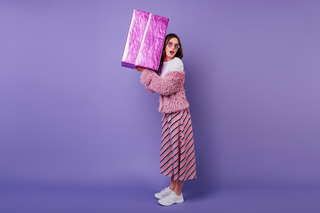 Full-length portrait of interested lady in white sneakers holding big present box. glamorous birthday girl.