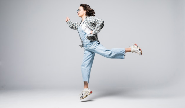 Full length portrait of a joyful young woman jumping and celebrating