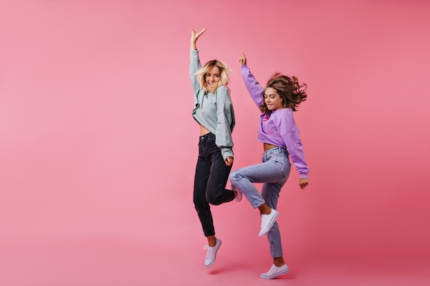 Full-length portrait of jumping white girls expressing happy emotions. portrait of best friends funny dancing together.
