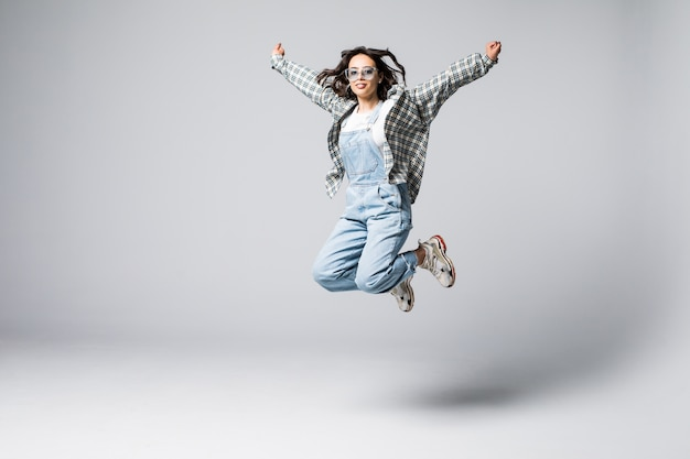 Full length portrait of a laughing woman jumping. looking
