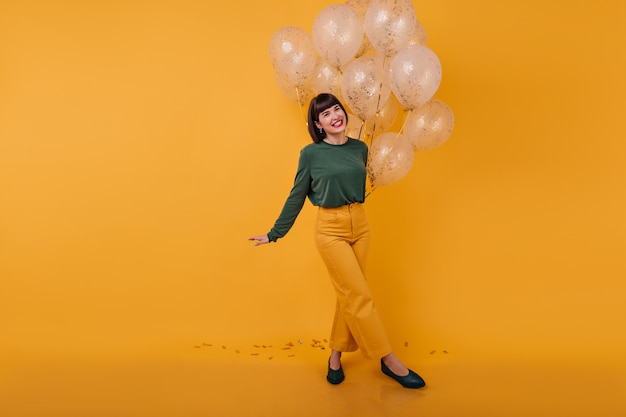 Full-length portrait of laughing woman standing with legs crossed. indoor shot of romantic birthday girl dancing with golden balloons.