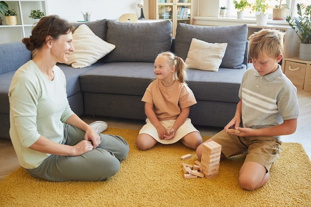 Full length portrait of loving family with special needs child playing board games while sitting on floor at home, copy space