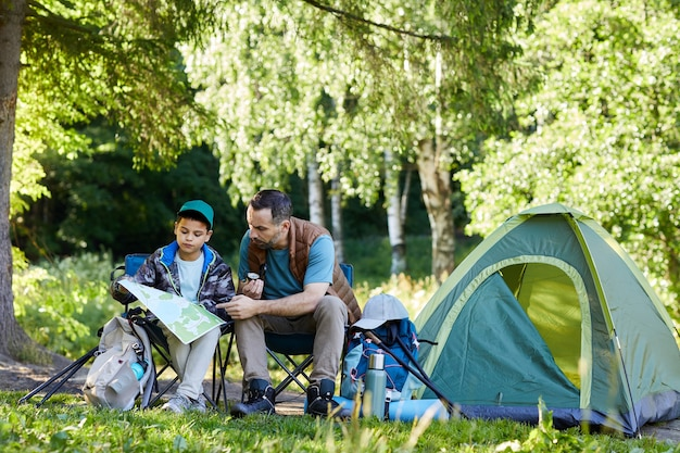 Full length portrait of loving father and son looking at map while enjoying camping trip together in nature, copy space