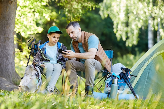 Full length portrait of loving father and son looking at smartphone while enjoying camping trip together in nature, copy space