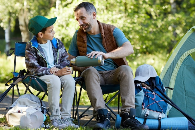 Full length portrait of loving father and son sharing hot drink while enjoying camping together in nature, copy space