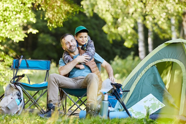 Full length portrait of loving father and son  and smiling happily while enjoying camping trip together in nature, copy space