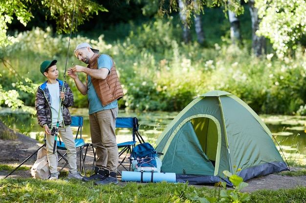 Full length portrait of loving father teaching son to set up fishing equipment while enjoying camping trip together, copy space