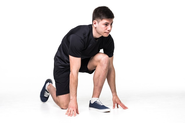 Ritratto integrale di un atleta maschio pronto per l'esecuzione isolato sul muro bianco