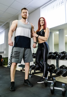 Full length portrait of a male bodybuilder and a muscular woman in gym.