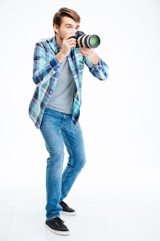 Full length portrait of a male photographer making shot on photo camera isolated on a white background