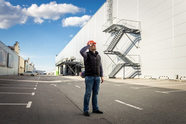 Full length portrait of male worker posing on parking of industrial building