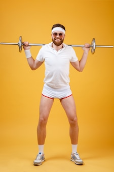 Full length portrait of a man athlete exercising with barbell