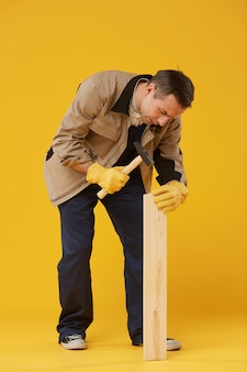 Full length portrait of mature worker hammering nail into wooden plank