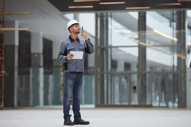Full length portrait of mature worker speaking by walkie-talkie while supervising work at construction site or in industrial workshop,