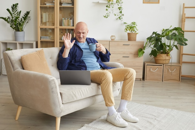 Full length portrait of modern senior man waving at laptop camera and smiling happily during video call at home
