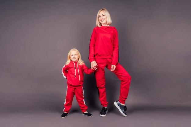 스포츠 정장을 입은 딸과 함께 전체 길이 초상화 어머니. 빨간색 세련된 정장 스튜디오 검정색 배경에서 포즈를 취한 어린 소녀와 함께 아름다운 젊은 금발 여성, 활동적인 스포츠 가족 힙합 댄서.