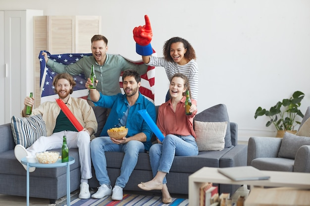 Full length portrait of multi-ethnic group of friends watching sports match on tv and cheering emotionally while holding american flag