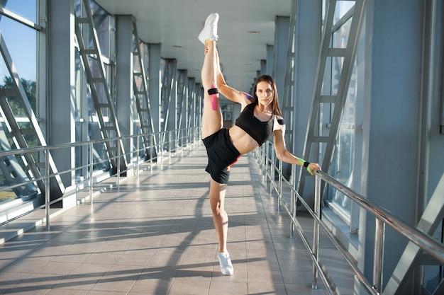 Full length portrait of muscular brunette woman practicing split