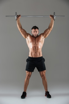 Full length portrait of a muscular serious shirtless male bodybuilder