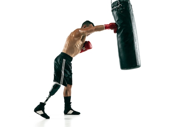 Full length portrait of muscular sportsman with prosthetic leg, copy space. male boxer in red gloves training and practicing. isolated on white  wall. concept of sport, healthy lifestyle.