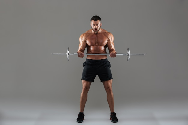 Full length portrait of a muscular strong shirtless male bodybuilder