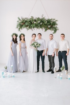 Full length portrait of newlywed couple and their friends at the wedding party