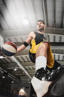 Полнометражный портрет баскетболиста с мячом на сером фоне тренажерного зала