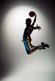 Полная длина портрет баскетболиста с мячом