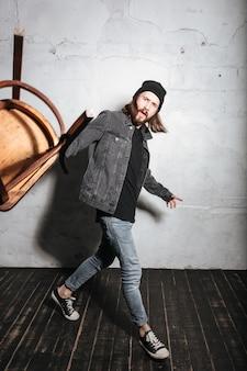 Полнометражный портрет бородатого хипстера в шляпе, бросающего стул спереди, изолированного над стеной