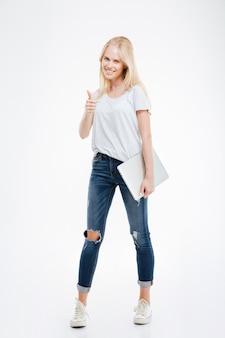 Портрет красивой девушки в полный рост, держащей ноутбук и показывающей жест, изолированный на белом
