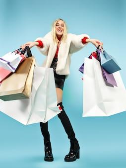 青いスタジオの背景の上に分離されたカラフルなショッピングバッグを持って歩いている美しい笑顔の面白い金髪の女性の完全な長さの肖像画。