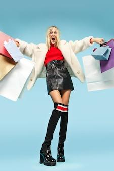 カラフルな買い物袋を持って歩く美しい笑顔の面白いブロンドの女性の全身像
