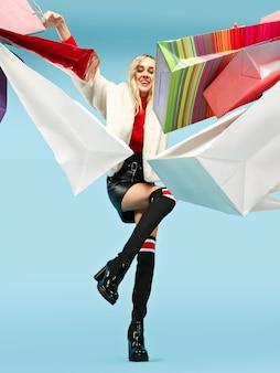 화려한 쇼핑 가방과 함께 걷는 아름다운 웃는 재미 금발 여자의 전체 길이 초상화