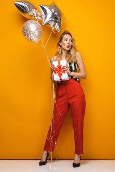 黄色の背景の上に立って、ギフトボックスと風船を保持している美しい若いブロンドの女性の完全な長さの肖像画
