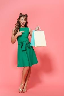 Портрет красивой молодой девушки пин ап в платье, стоящей изолированно, с сумками для покупок