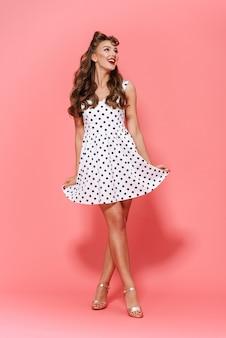 Полная длина портрет красивой молодой девушки пин ап в платье стоя изолированно, позирует