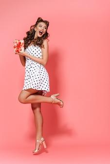 孤立して立っているドレスを着て、ギフトボックスを示す美しい若いピンナップガールの全身像
