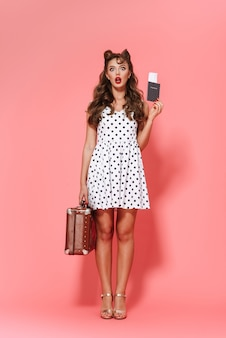 Полнометражный портрет красивой молодой девушки в стиле кинозвезды в платье, стоящей изолированно, показывая паспорт с авиабилетом, неся чемодан